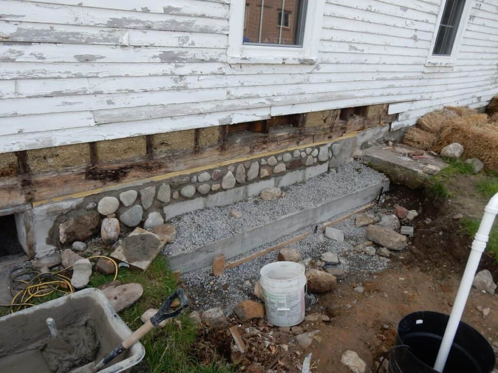 Field stones are placed on the face of the blocks to blend the new with the old.