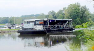 The GlassBarge passing the Mid Lakes marina heading east.